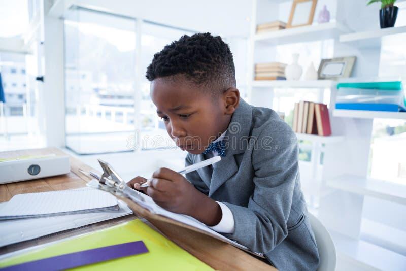 O menino que imiting como a escrita do homem de negócios no papel uniu à prancheta foto de stock