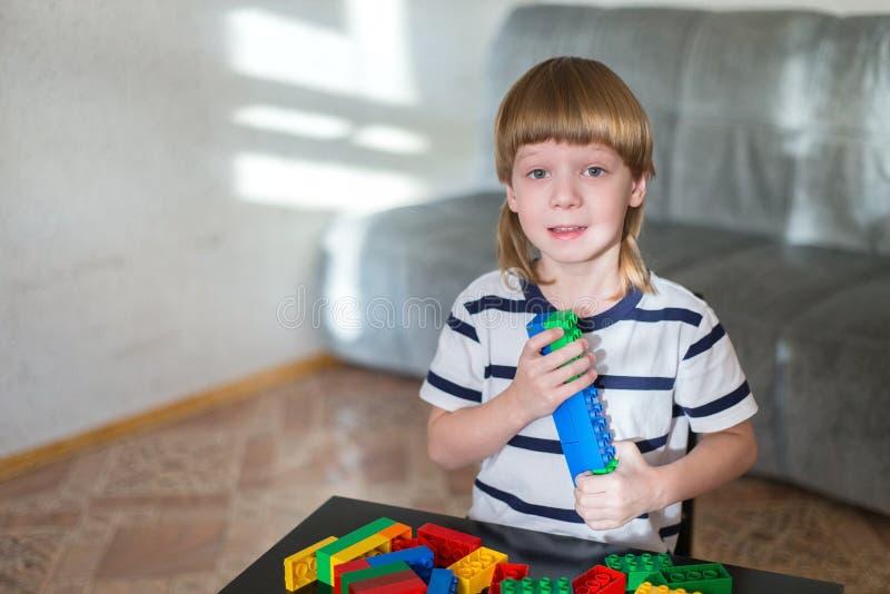 O menino que joga com lotes do plástico colorido obstrui interno imagem de stock
