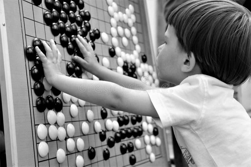 O menino que joga o jogo chinês vai imagem de stock royalty free