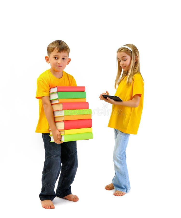 O menino que leva livros pesados, menina tem um eBook fotografia de stock royalty free