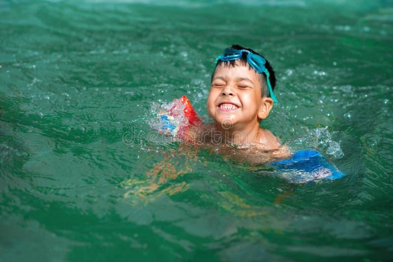 O menino que a morena com óculos de proteção em uma testa se banha alegremente na água imagens de stock