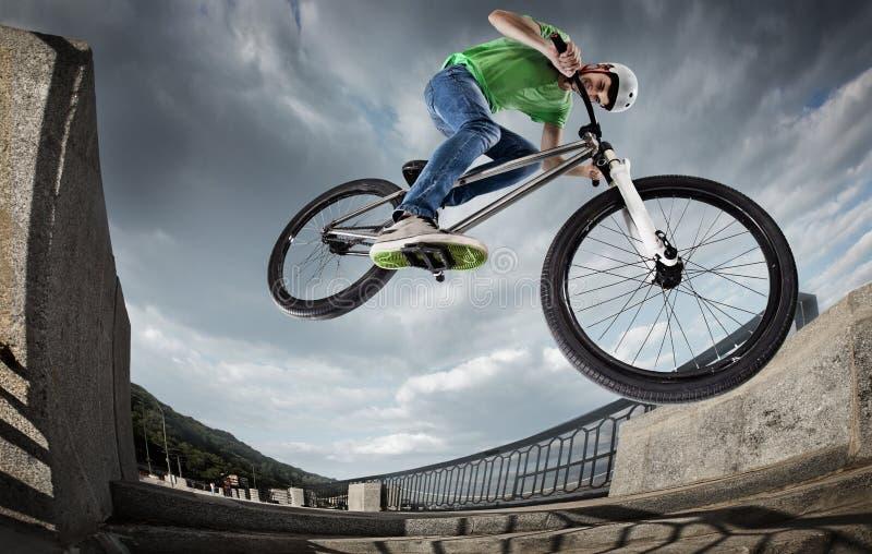 O menino que salta com sua rua-bicicleta na cidade foto de stock