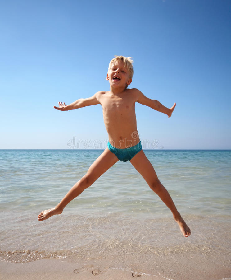 O menino que salta em um mar imagens de stock