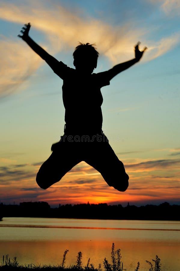 O menino que salta no campo de trigo foto de stock royalty free