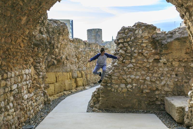 O menino que salta no ruínas fotografia de stock royalty free