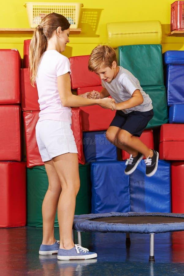 O menino que salta no trampolim no gym foto de stock