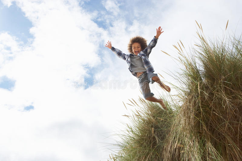 O menino que salta sobre a duna imagens de stock