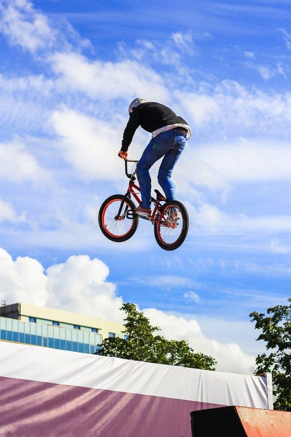 O menino que salta uma elevação aturde em um Mountain bike O cavaleiro novo na roda de seu bmx faz um truque Passeios do motocicl fotografia de stock