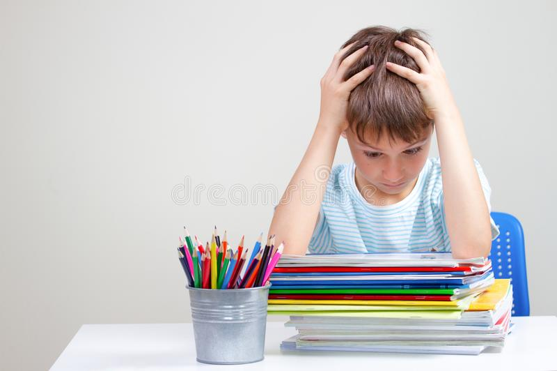 O menino que senta-se e que olha dentro aos livros e aos cadernos Educação, escola, conceito das dificuldades de aprendizagem foto de stock