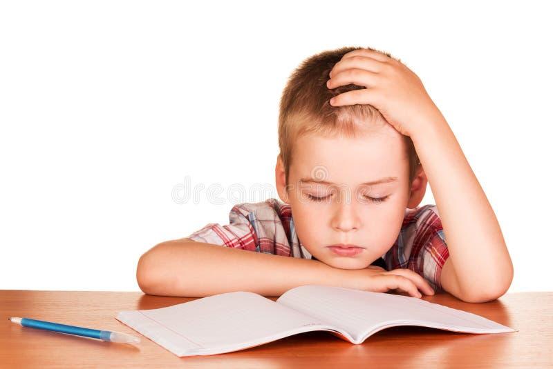 O menino que senta-se na tabela caiu adormecido no livro de exercício isolado imagem de stock royalty free