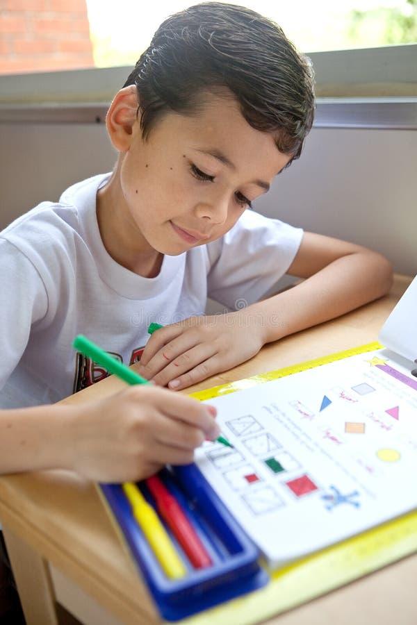 O menino redige fazer seus trabalhos de casa da escrita imagens de stock royalty free