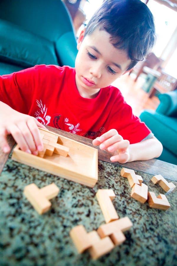 O menino redige no jogo de madeira da serra de vaivém. fotos de stock royalty free