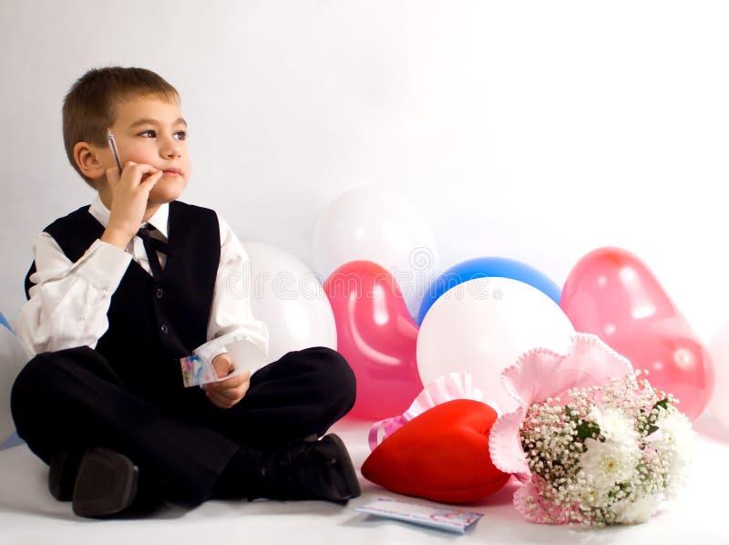 O menino reflete em umas felicitações ao dia do Valentim imagens de stock
