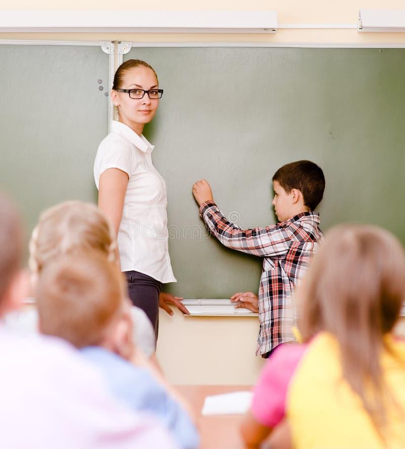O menino responde a perguntas dos professores perto de uma administração da escola fotografia de stock