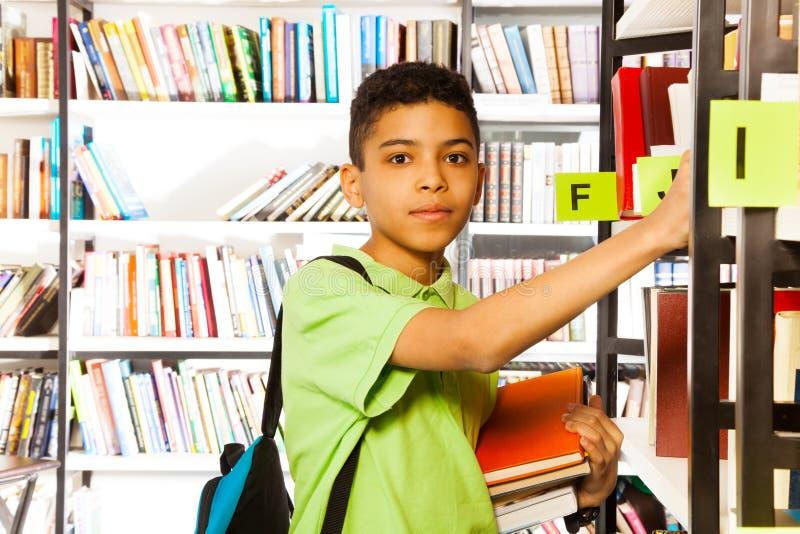 O menino sério olha e procura o livro na prateleira fotografia de stock
