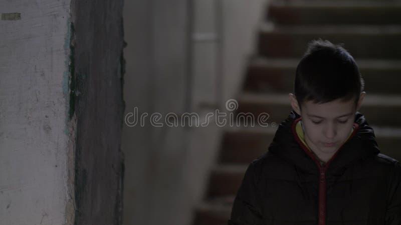 O menino só de uma família pobre está em uma casa dilapidada fotografia de stock