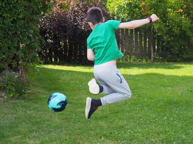 O menino salta com a bola fotografia de stock royalty free