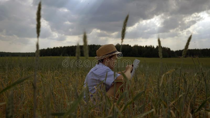 O menino senta-se em um campo contra nuvens bonitas e usa-se uma tabuleta na noite fotografia de stock