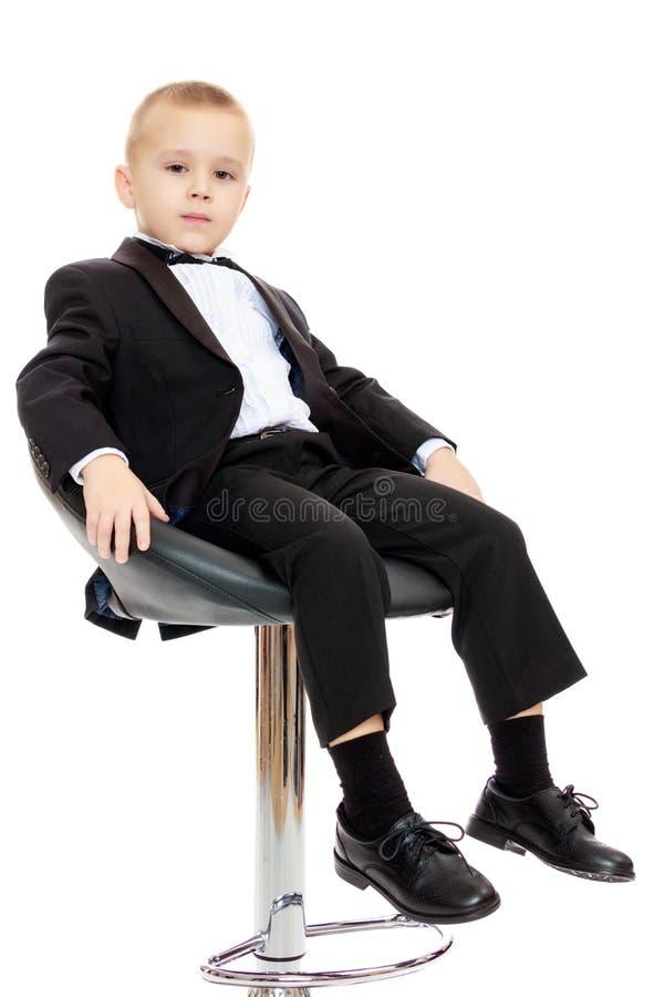 O menino senta-se em uma cadeira de giro imagens de stock royalty free