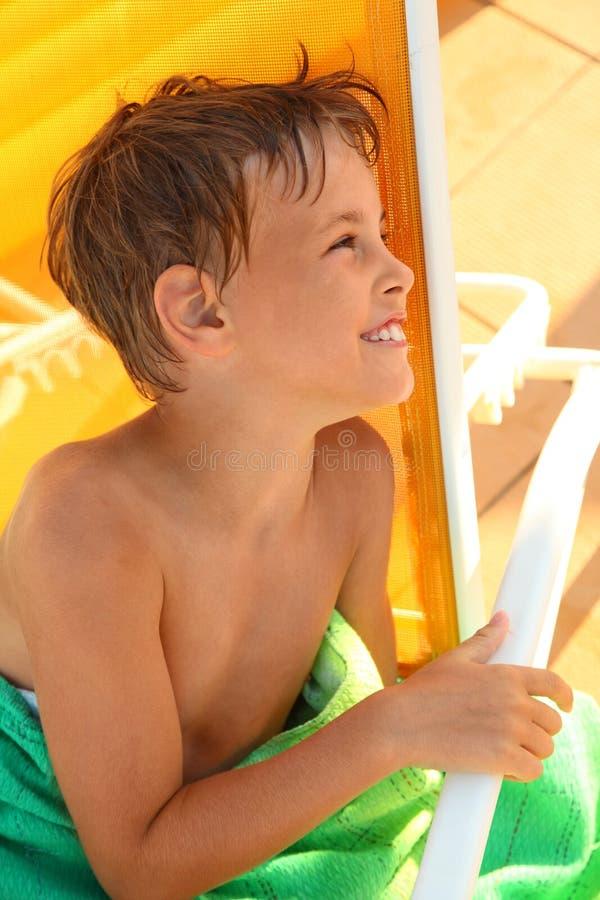 O menino senta-se na cadeira de plataforma amarela imagens de stock royalty free