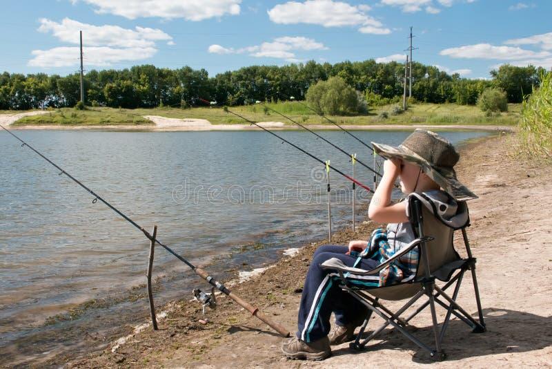 O menino senta-se na costa da lagoa e olha-se no distanc fotografia de stock