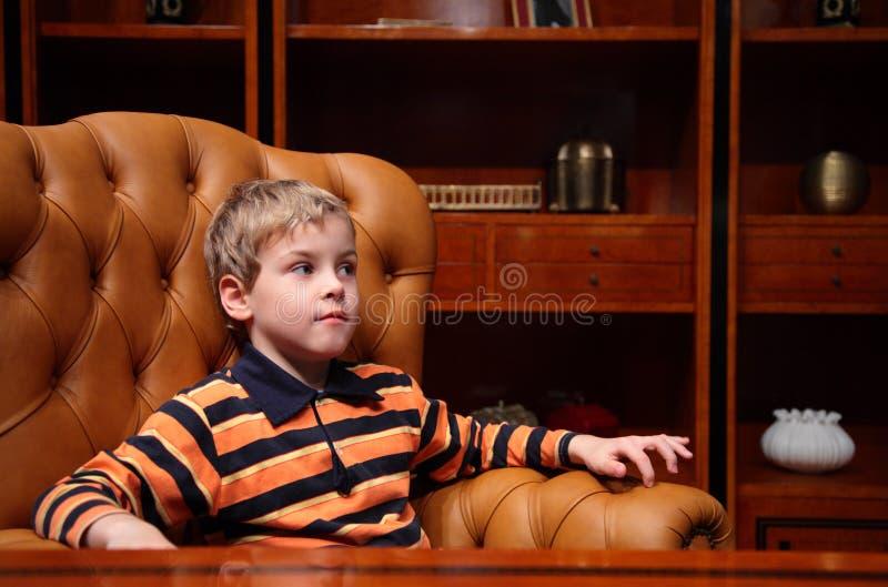 O menino senta-se na poltrona de couro no escritório imagens de stock
