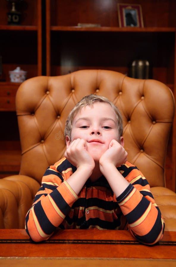 O menino senta-se na poltrona no escritório luxuoso fotos de stock