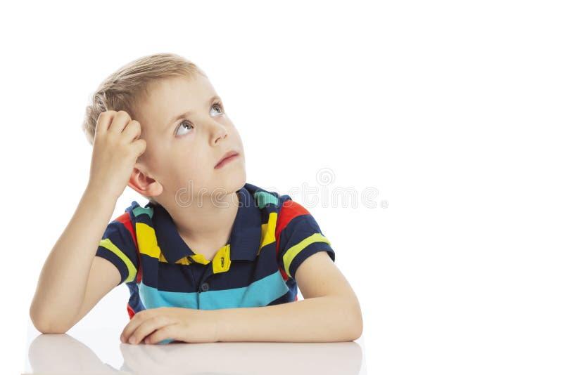 O menino senta-se na tabela e risca-se sua cabeça Isolado em um fundo branco foto de stock