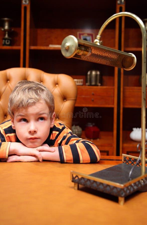 O menino senta-se no escritório luxuoso imagens de stock royalty free