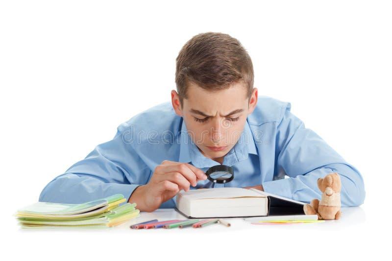 O menino senta-se perto da mesa com as fontes de escola isoladas no fundo branco foto de stock