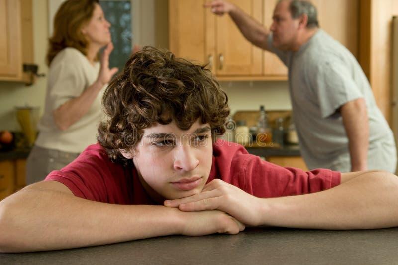 O menino sofre enquanto os pais lutam no fundo foto de stock