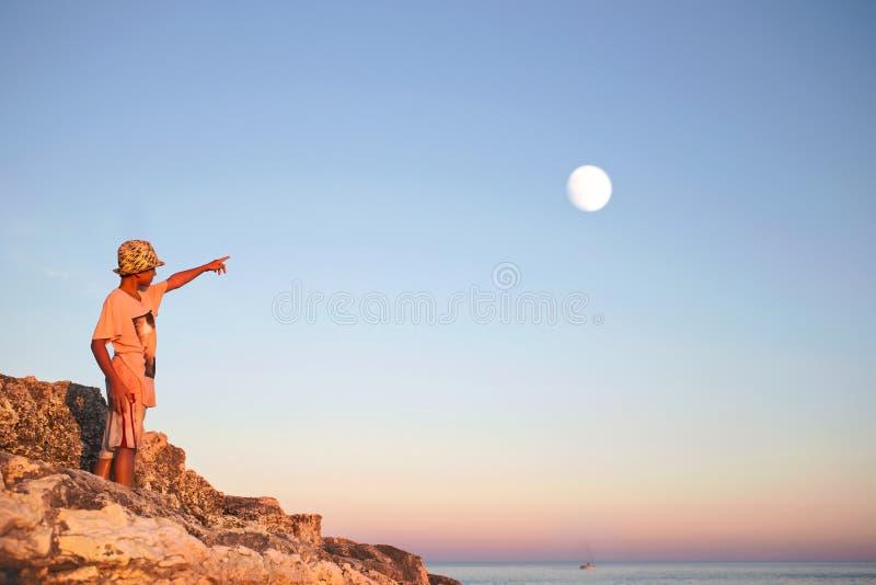 O menino sonhador aponta seu dedo com a lua no céu foto de stock