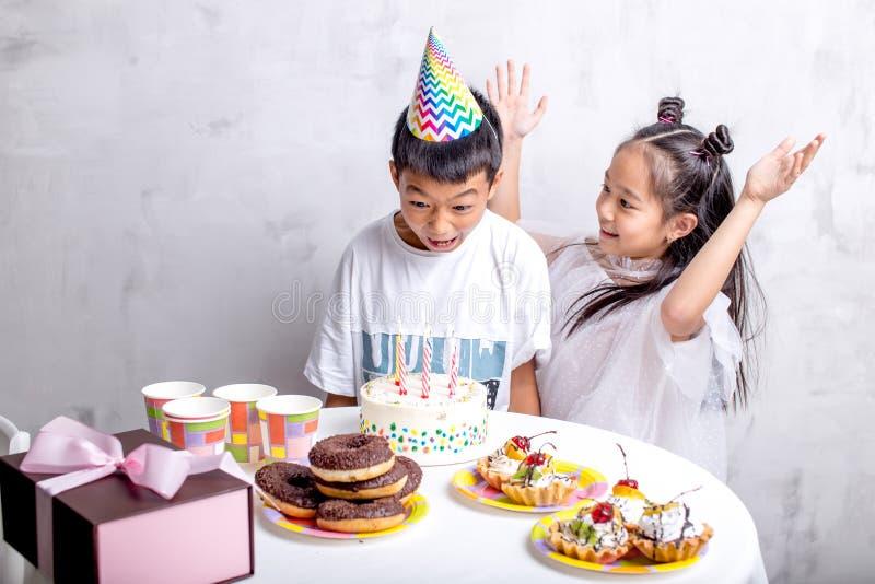 O menino surpreendido irritado não está feliz ter o bolo pequeno foto de stock