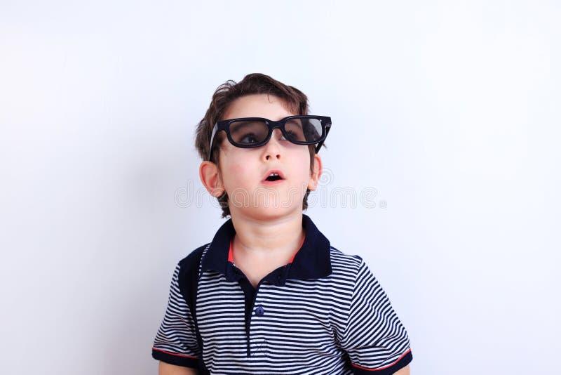 O menino surpreendido ou entusiasmado que olha através dos óculos de sol, estúdio shoo imagens de stock royalty free