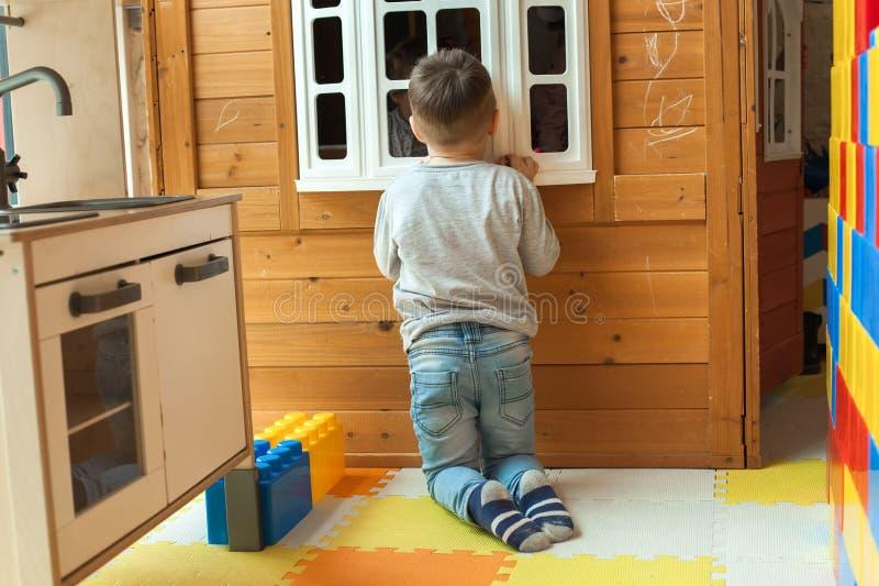 O menino tem 4 anos velho, os jogos louros no campo de jogos dentro, espreitadelas para fora a janela da casa de madeira do brinq fotos de stock