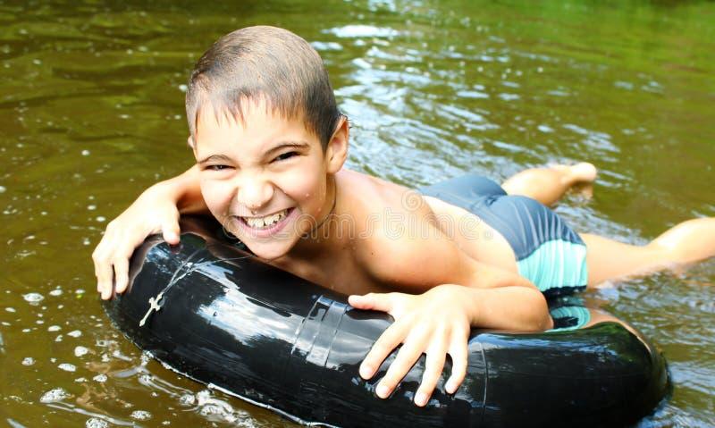 O menino tem o divertimento em uma tubulação no rio imagem de stock