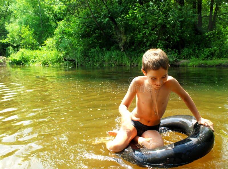 O menino tem o divertimento em uma tubulação no rio fotografia de stock royalty free