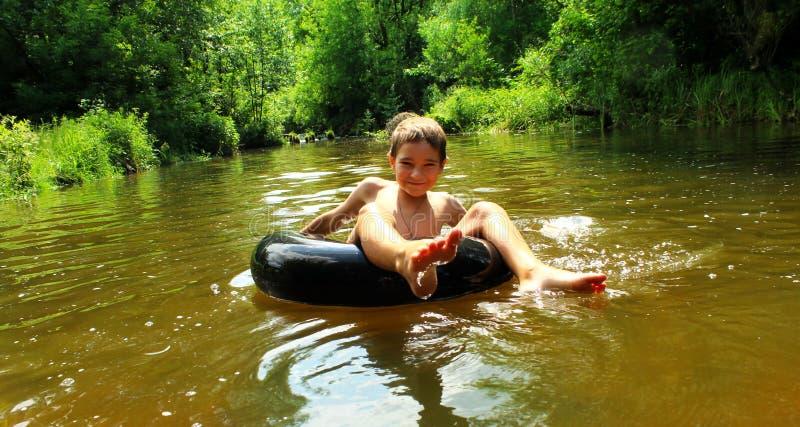 O menino tem o divertimento em uma tubulação no rio imagem de stock royalty free
