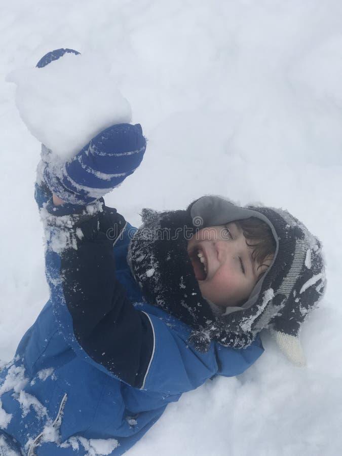 O menino tem realmente o divertimento após encontrado primeiramente com a neve fotografia de stock