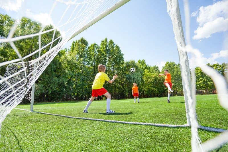 O menino tenta travar com suas mãos o futebol imagens de stock