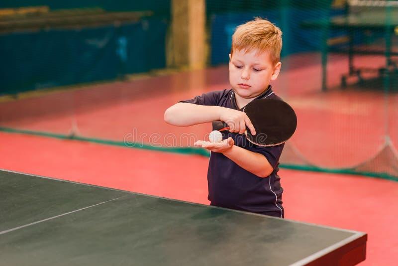 O menino toma a bola no tênis de mesa imagem de stock