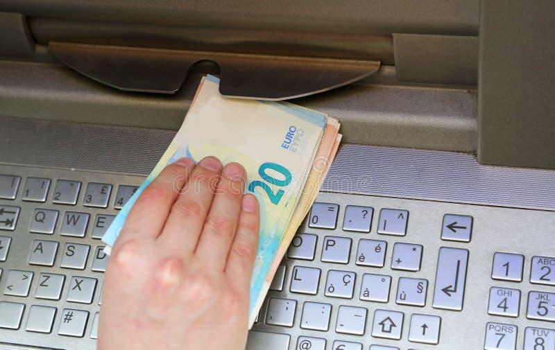 O menino toma o dinheiro de uma máquina do atm fotos de stock royalty free