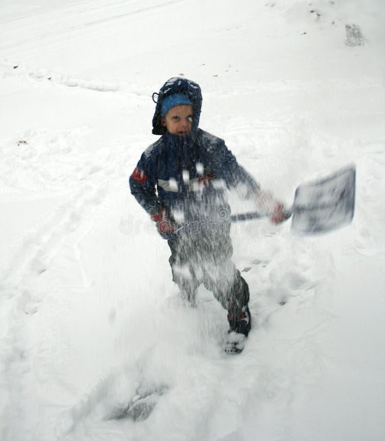 O menino trabalha com pá a neve imagens de stock