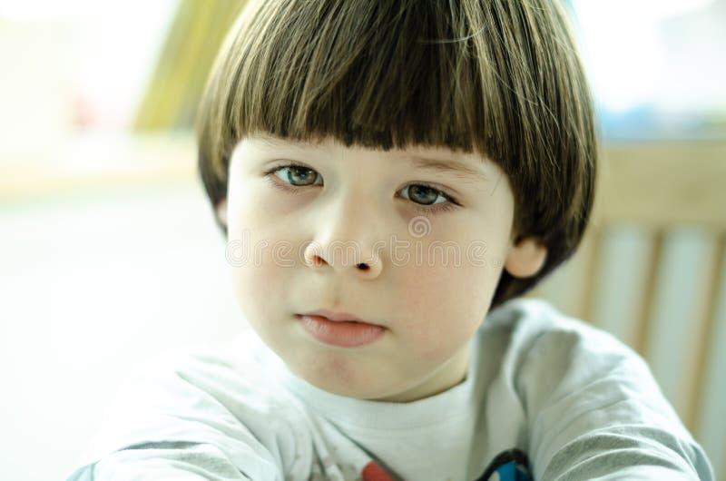 O menino triste é de assento e de vista na distância fotos de stock