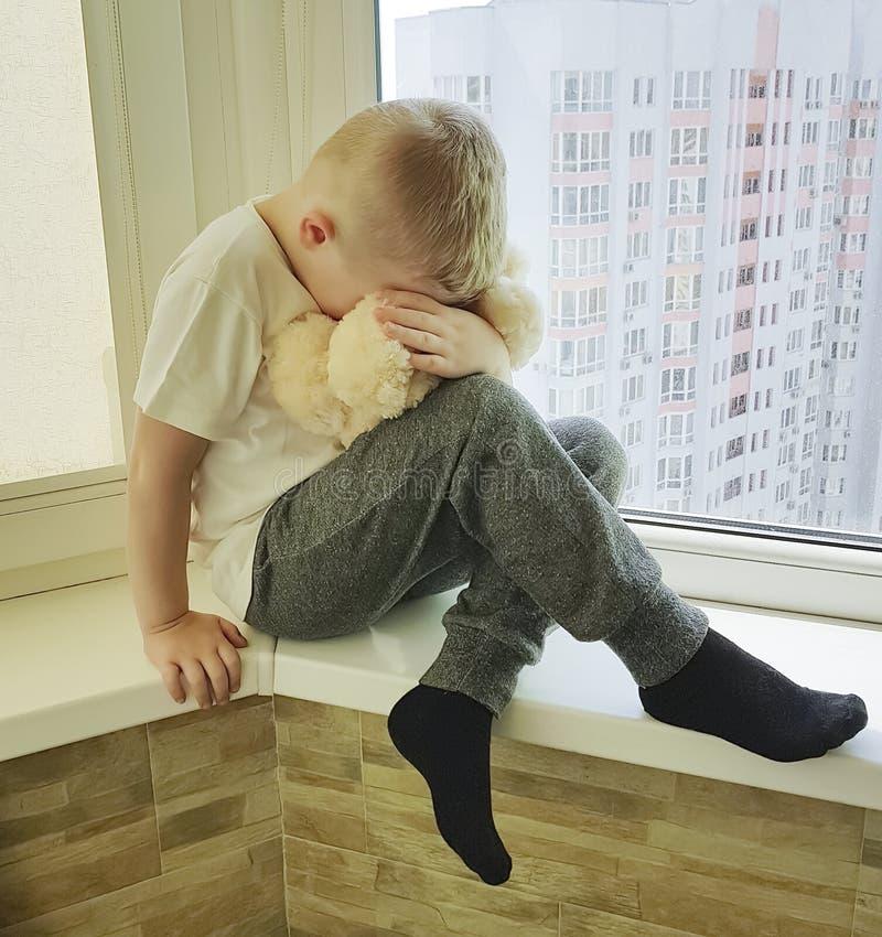 O menino triste pequeno senta os gritos do problema da expressão infelizes em uma janela com um urso de peluche só imagens de stock royalty free