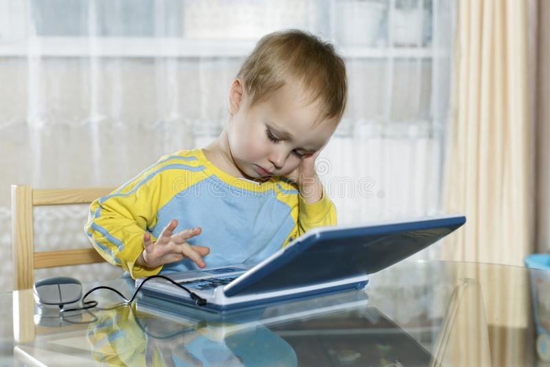 O menino usa um computador do ` s das crianças foto de stock