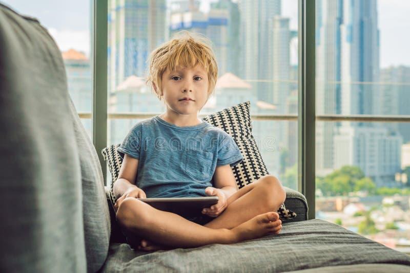 O menino usa uma tabuleta em casa no sofá no fundo de uma janela com arranha-céus As crianças modernas na megalópole usam Ta imagens de stock