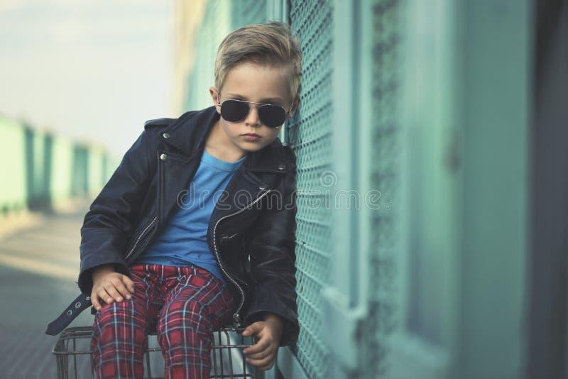 O menino, vestido moderna, levanta como um modelo imagens de stock