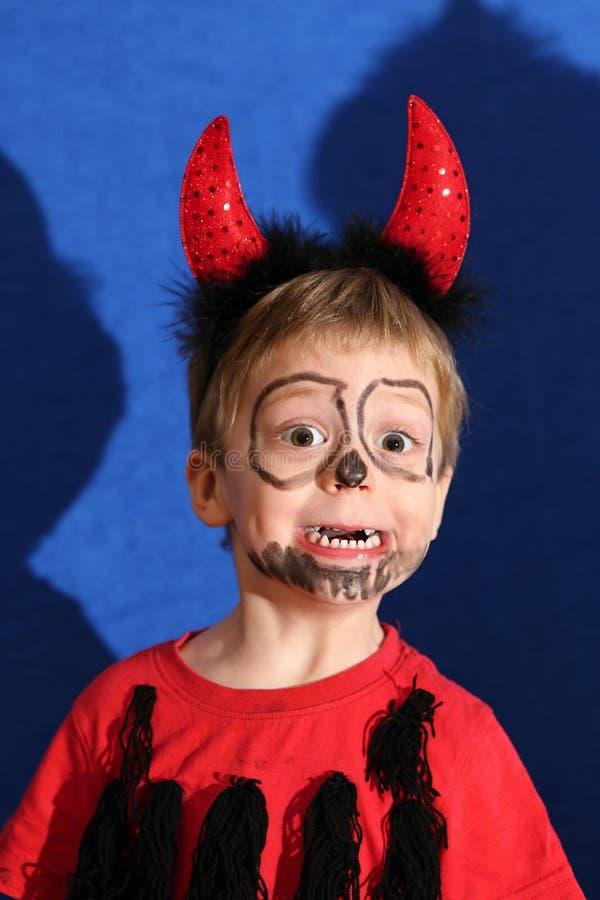 O menino vestiu-se para o diabo pequeno com os grandes quions vermelhos fotos de stock royalty free