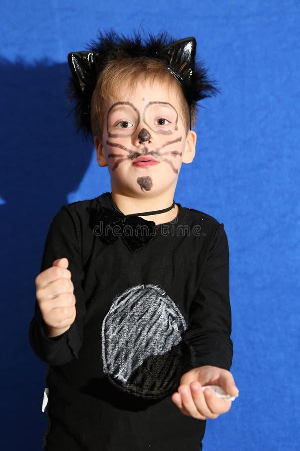 O menino vestiu-se para o gato preto pelo fundo azul imagem de stock royalty free
